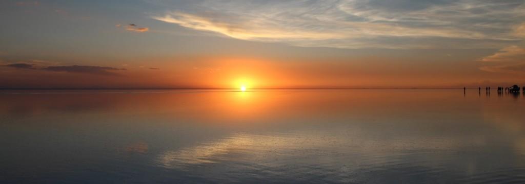 塩湖の水で消されるように太陽が小さくなっていく